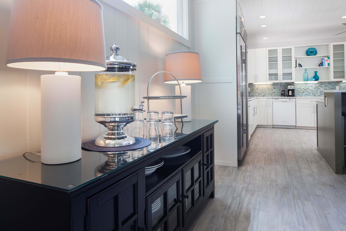Black credenza off of the kitchen with two large white lamps and a dispenser with water and lemon, rocks glasses and a two tiered platter for serving at Sea Oats Estate in Captiva Island, FL