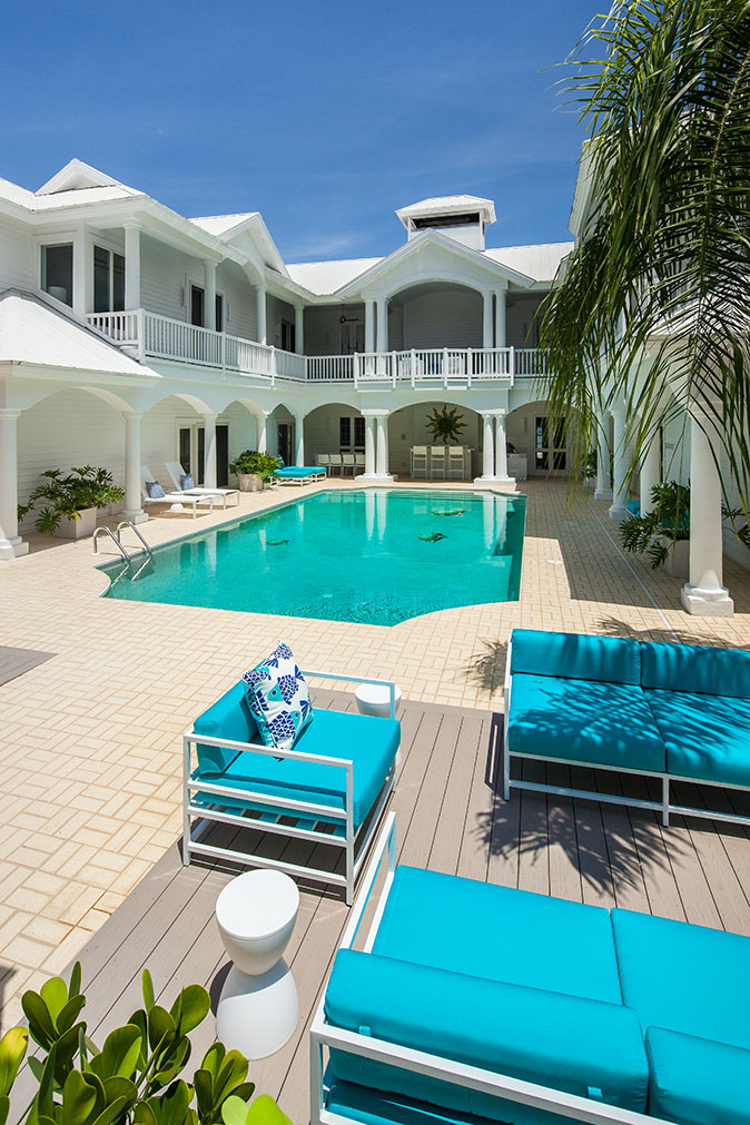 White Estate in Captiva Island, FL with an in-ground pool, blue patio furniture, white pool chairs, a patio area with green plants and a second floor balcony overlooking the pool surrounded by palm trees