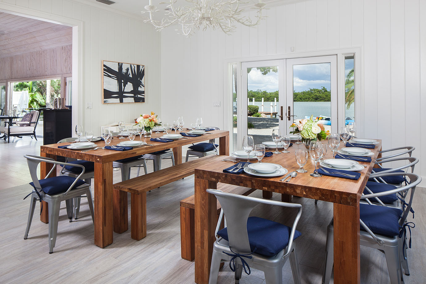 Two rectangular dining tables set with dinnerware, water and wine glasses with a bright colored bouquet of flowers in the center with silver gunmetal chairs with navy blue cushions