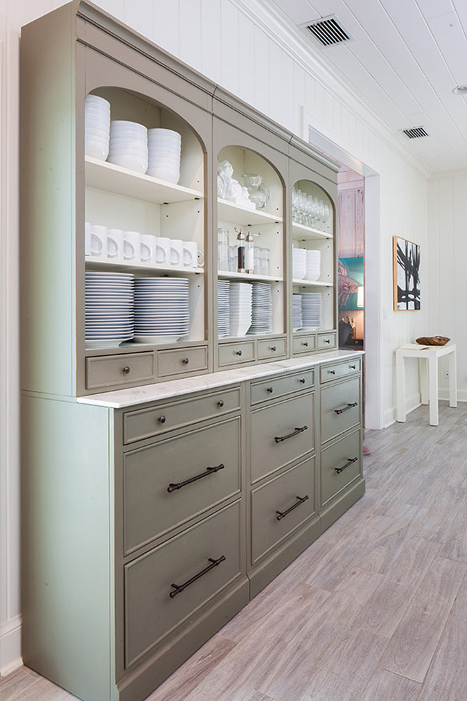 Gray credenza off the kitchen storing white plates and bowls, coffee cups, wine glasses and rocks glasses in Captiva Island, FL estate