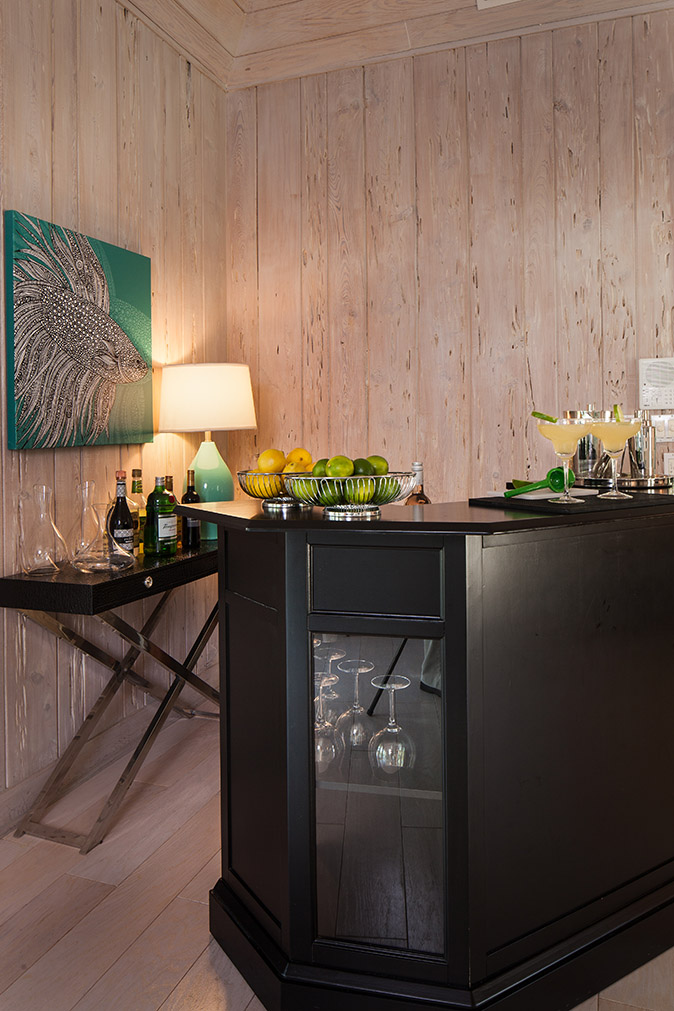Black wooden bar with a basket of lemons and limes and margaritas on the bar top; a back bar table with wine and liquor on it with decanters and a blue lamp surround by wooden plank walls at Sea Oats Estate in Captiva Island, FL