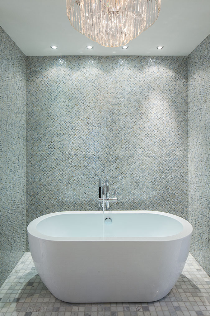 White soaking tub in the Sea Oats Estate in Captiva Island, FL surrounded by tiled walls and a crystal chandelier