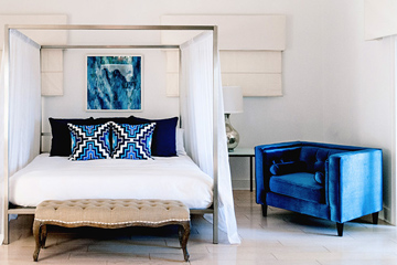 Luxurious guest room with a canopy bed draped with white sheer curtains, white bedding, navy blue and bright blue aztec pillows, a sitting bench at the foot of the bed and a velvet blue lunge chair at the estate in Captiva Island, FL