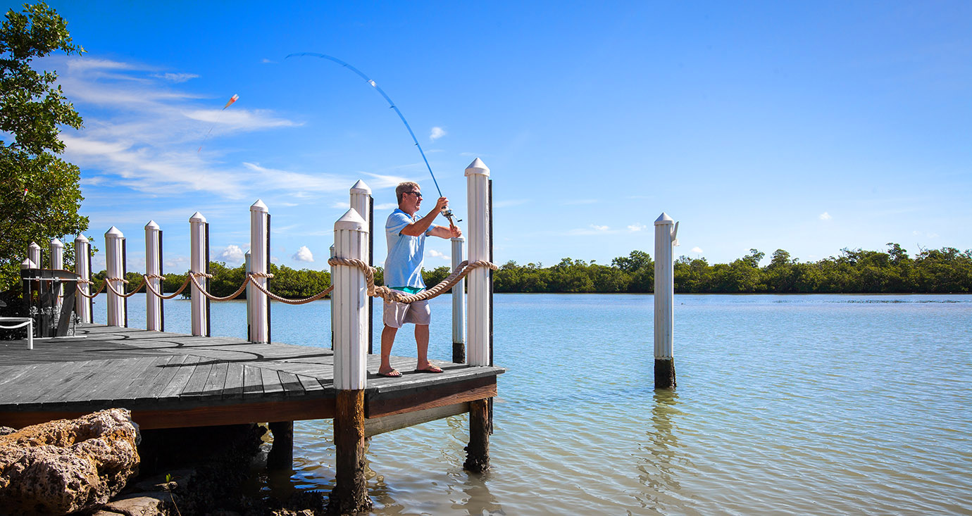 Man fishing off the end of the dock casting a fishing pole into the ocean in Captiva Island, FL