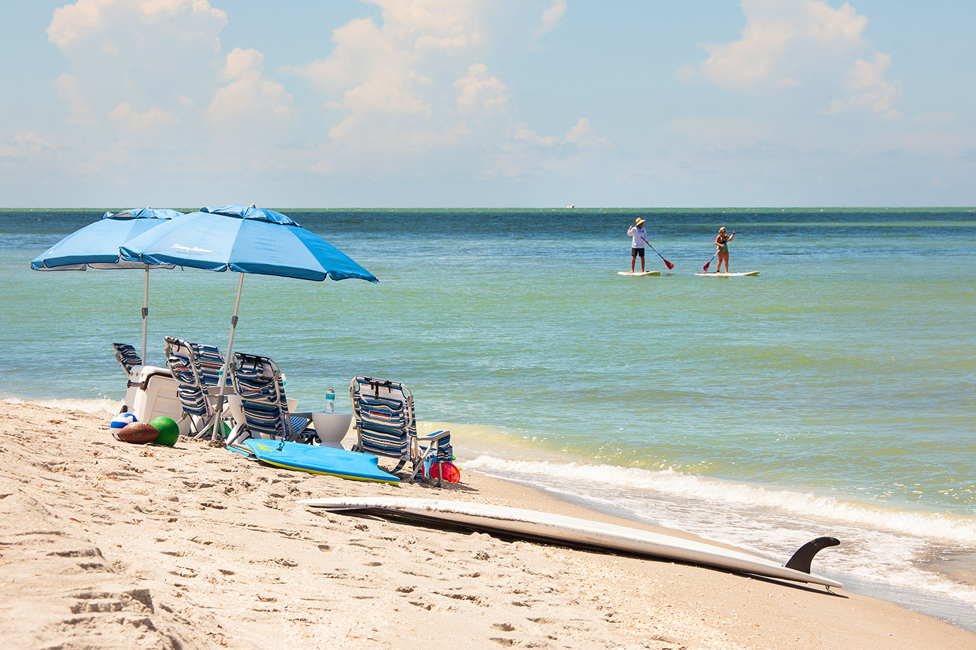 Shore line in Captiva Island, FL with five beach chairs and two umbrellas white two people paddle board in the ocean in the distance