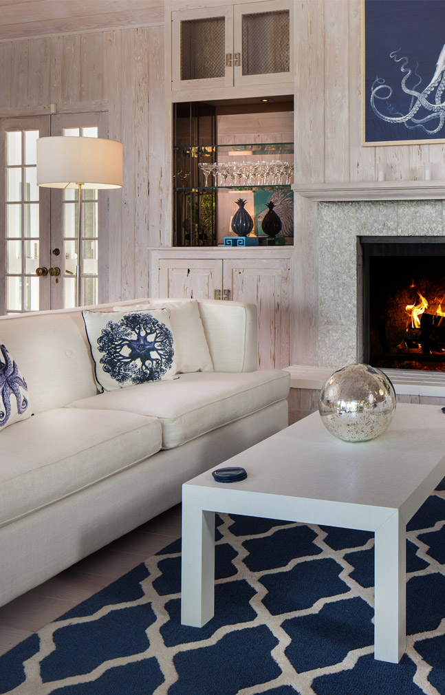 Living room at the Sea Oats Estate in Captiva Island, FL with ahote couches, a white wooden coffee table, an a blue and white area rug; a fireplace and mantle with glass shelving and cabinets and coastal decorations throughout